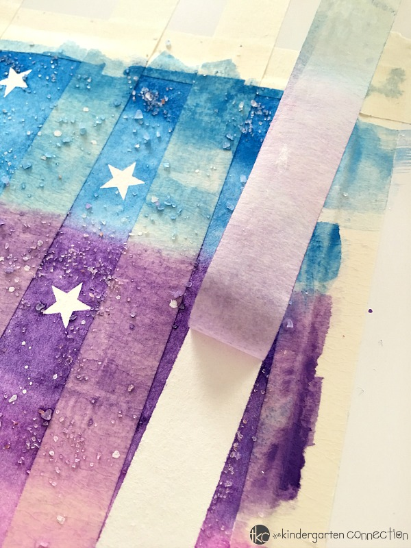 Create a bright, textured winter watercolor scene of tree trunks in a night sky with this watercolor resist painting activity.