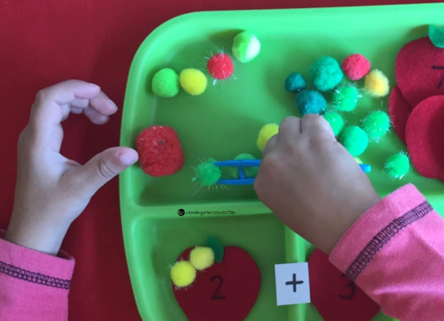 Here is a fun Apple themed hands-on math idea for you: apple sums! Make numbered felt apples and use pompoms as counters to work on sums plus fine motor skills!
