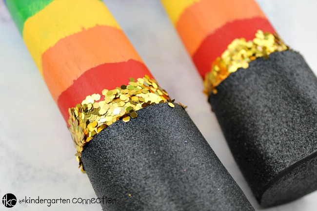 Rainbow Rain Stick Craft add a line of glue to the top of the black foam piece all the way around and then add chunky gold glitter