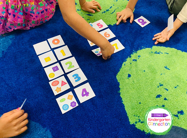 Students can take turns drawing button cards, counting, and finding their matching number cards.