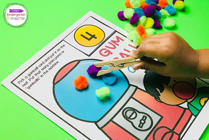 """In """"Gum Ball Drop"""", students strengthen counting skills by filling the gumball machine with the designated number of pom poms."""