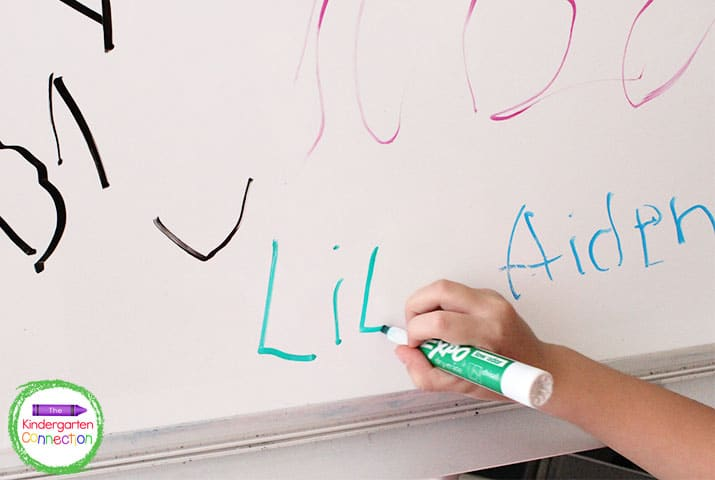 To keep this kindergarten routine simple, students use their name card to help them write their name on the easel.