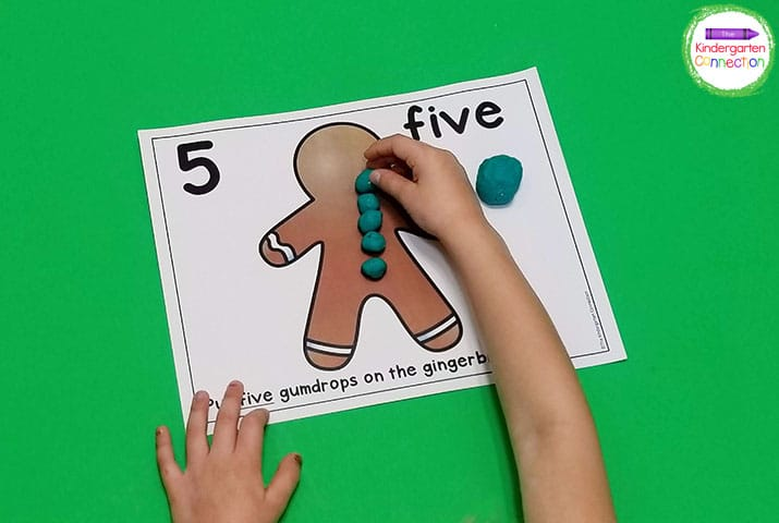 Roll up the correct number of play dough balls and place them on the gingerbread man play dough mat.