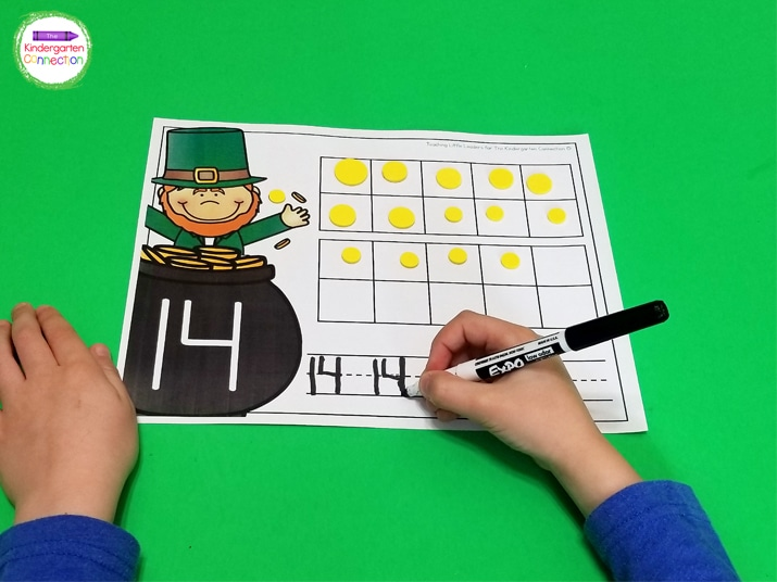 Students practice writing the number on the bottom of the counting mat.