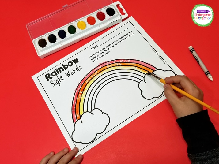 Then, we begin to paint the rainbow colors in order on top of our crayon sight words.
