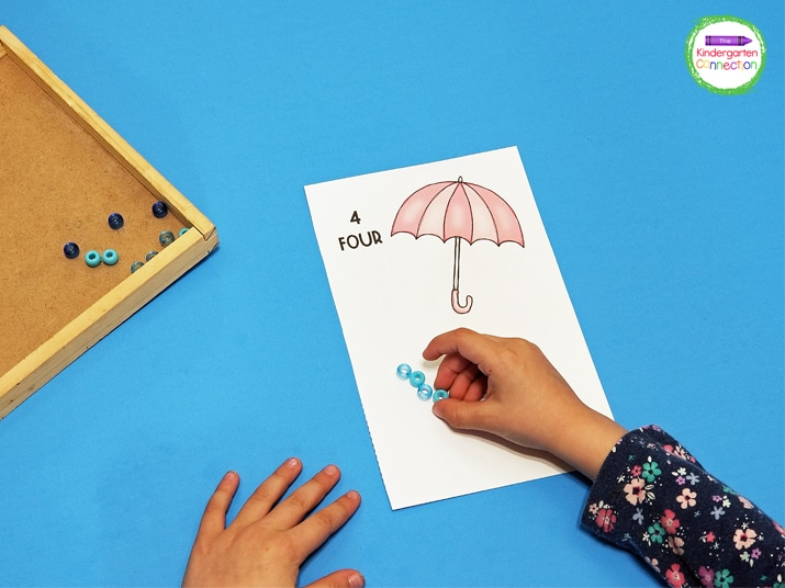 Students read the number on the umbrella counting card and add the corresponding number of manipulative for raindrops.