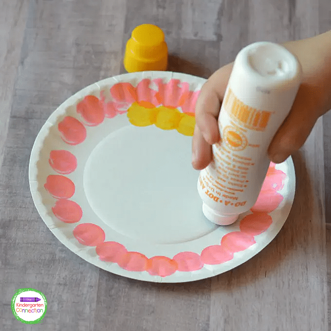 The kids start on the outside edge of the paper plate and go around the circumference of the plate stamping the dot markers until it is filled to the center.