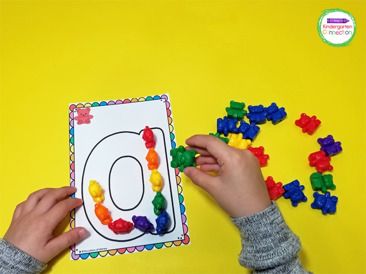 The kids must pick up the counting bears and place them carefully within the letters until they are filled up.