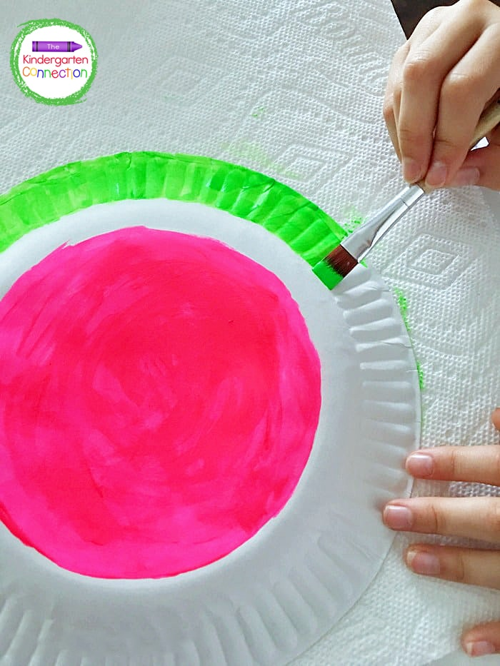 Next, kids can paint the rim of the paper plate with green tempera paint.