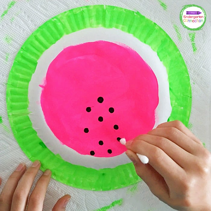 Invite your child to use a cotton swab dipped in black tempera paint to add the seeds.