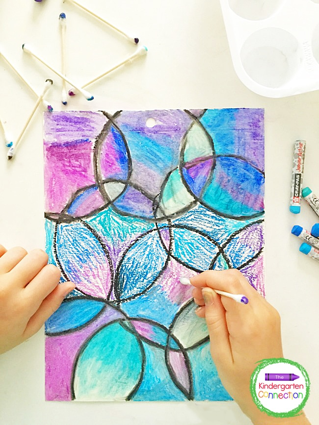 After students have traced and colored in the shapes with oil pastels, they can use the cotton swab dipped in baby oil to blend.