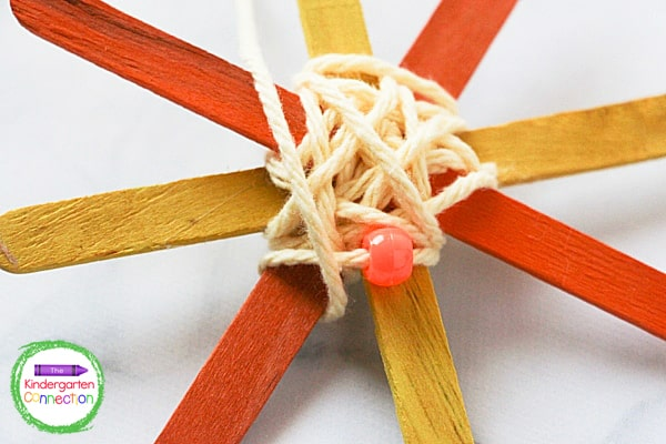 Your students will twist the yarn over the center of the popsicle stick frame until the center is covered.