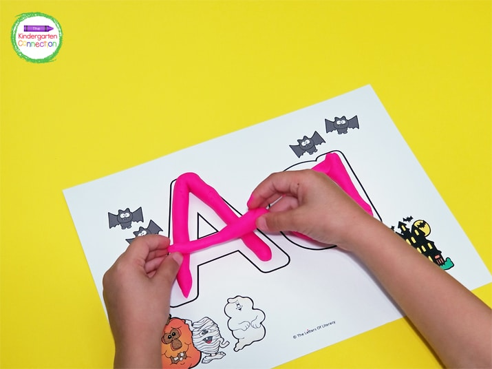The first way we use these alphabet play dough mats is by creating play dough snakes to fill in the letters.