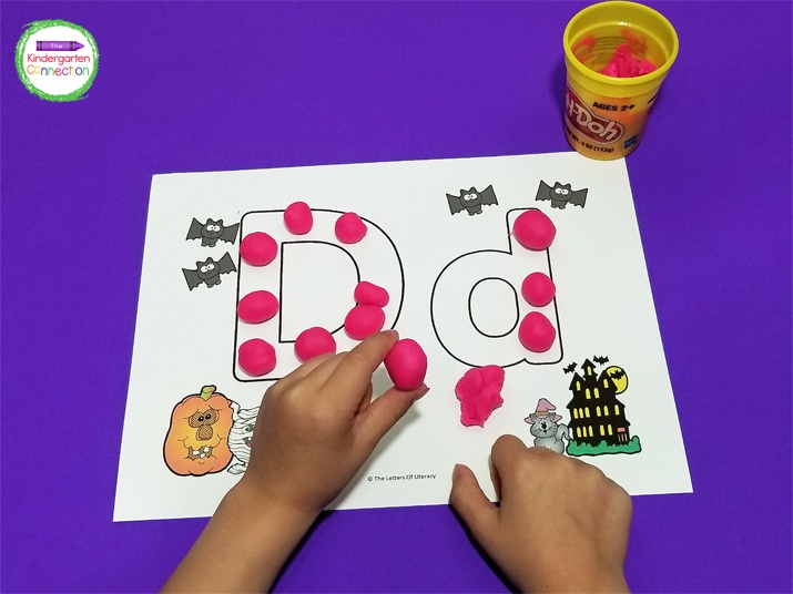 We also fill in the alphabet play dough mats with play dough balls.