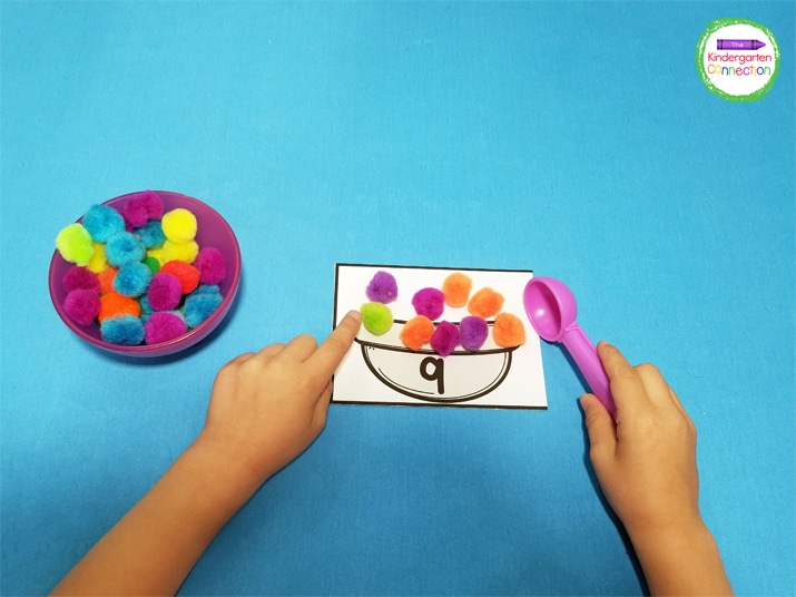 Using the spoon as the tool to pick up the pom poms is a great fine motor activity for hand control and scooping.