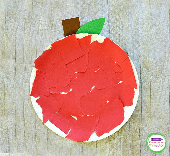 Glue the pieces of torn paper onto the paper plate to cover it completely so it looks like an apple.