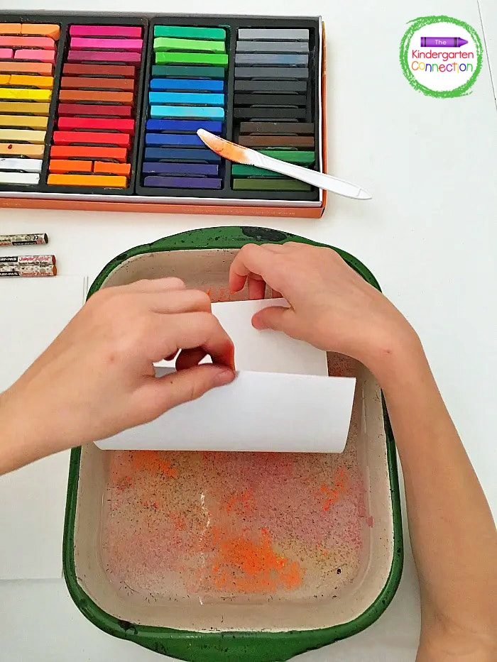 After the surface of the water is covered with chalk shavings, students can gently place a sheet of cardstock paper on top.