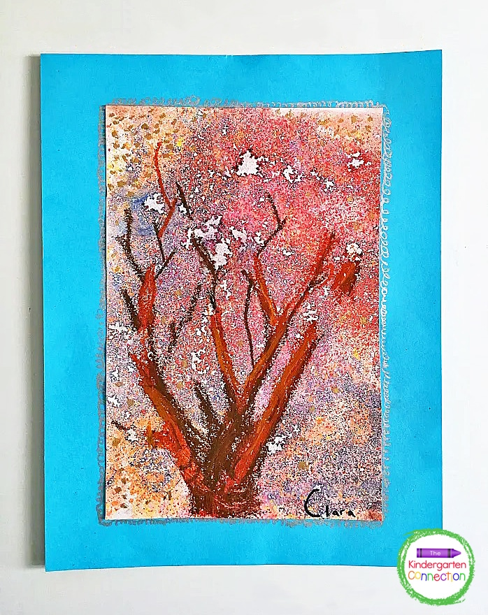 Once the paper is completely dry, invite students to use oil pastels (or crayons) to add a tree trunk and branches to their fall art project.