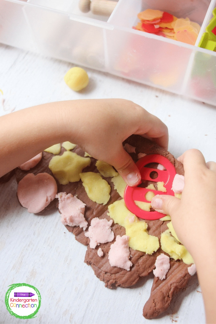 Using cookie cutters in the play dough is a great way to build and engage fine motor muscles.