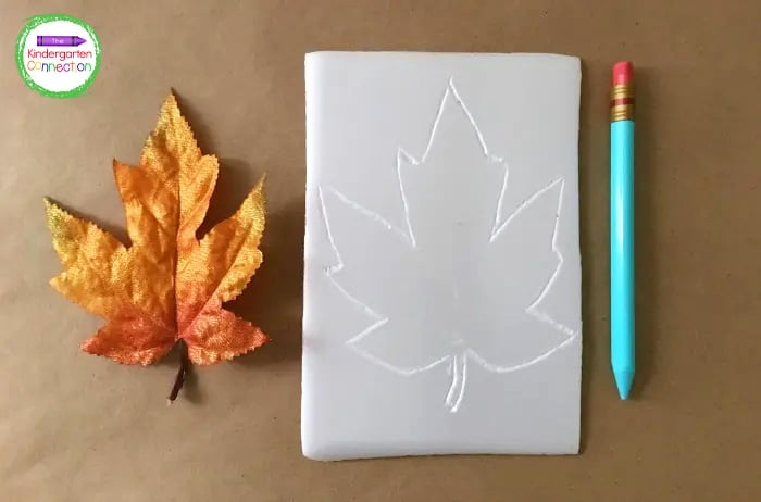 Next, use a dull pencil to trace the outline of a leaf onto the piece of foam tray.