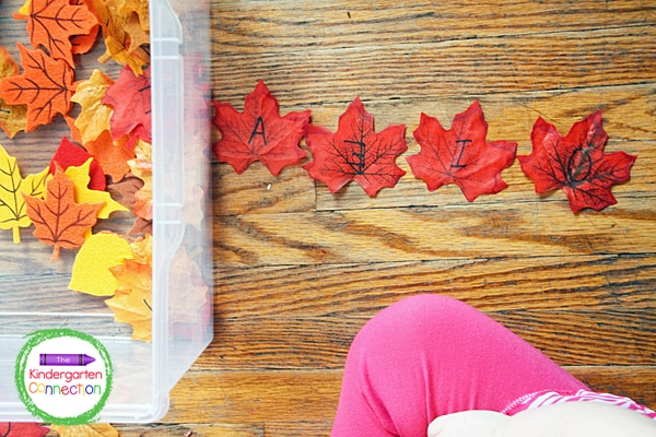 I had my kids sort through the sensory bin to find all of the vowels on red leaves.