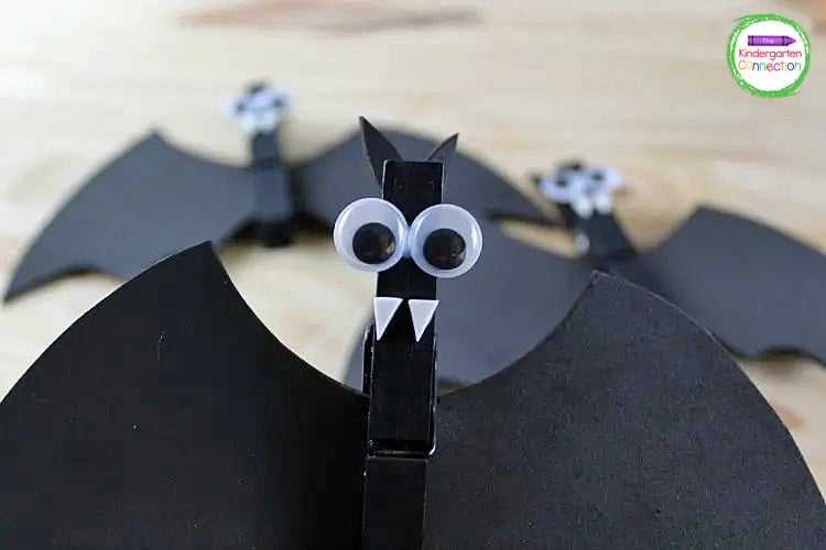 Glue the ears inside the top of the clothespin, glue on googly eyes, and glue the white fangs under the googly eyes to make the bat.