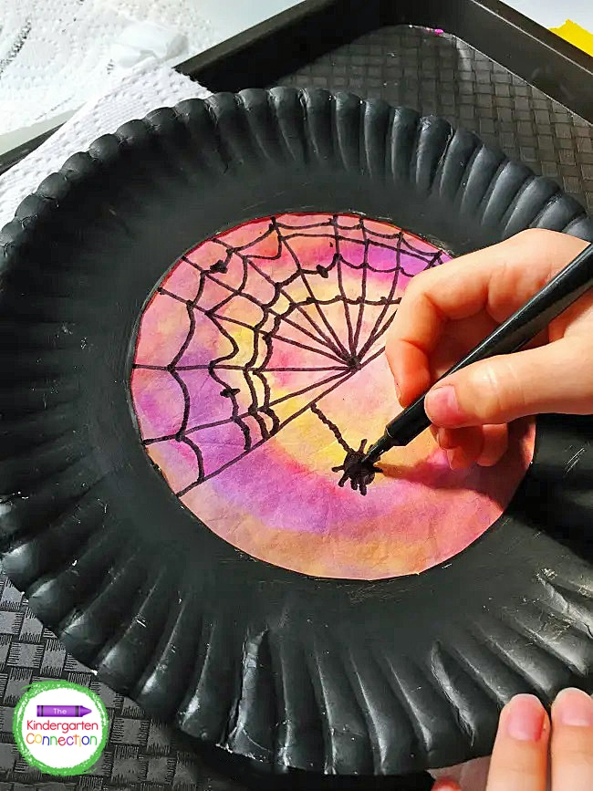 Invite your students to use washable black felt tip markers to lightly draw spooky details like webs and spiders.