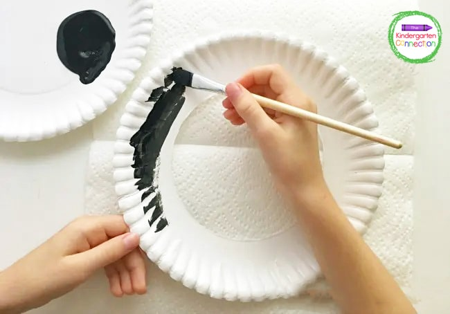 Cut the center out of a paper plate and invite your students to use black washable paint to cover the paper plate rim.