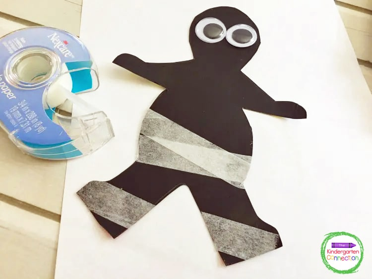 Start taping your mummy, overlapping each piece of tape and folding the edges over to the backside of the mummy.