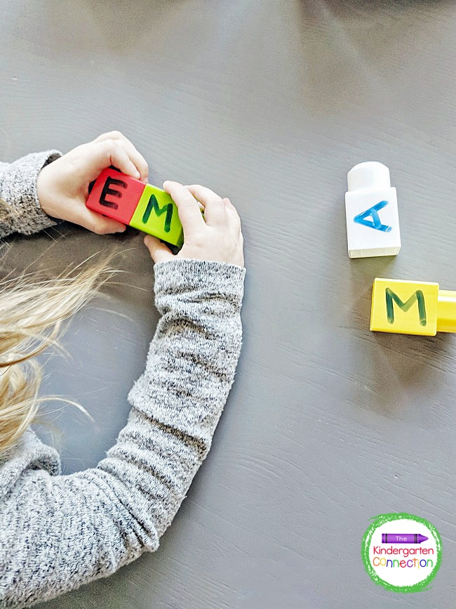 For our final name spelling practice idea, I wrote letters on our plastic blocks using a dry-erase marker.