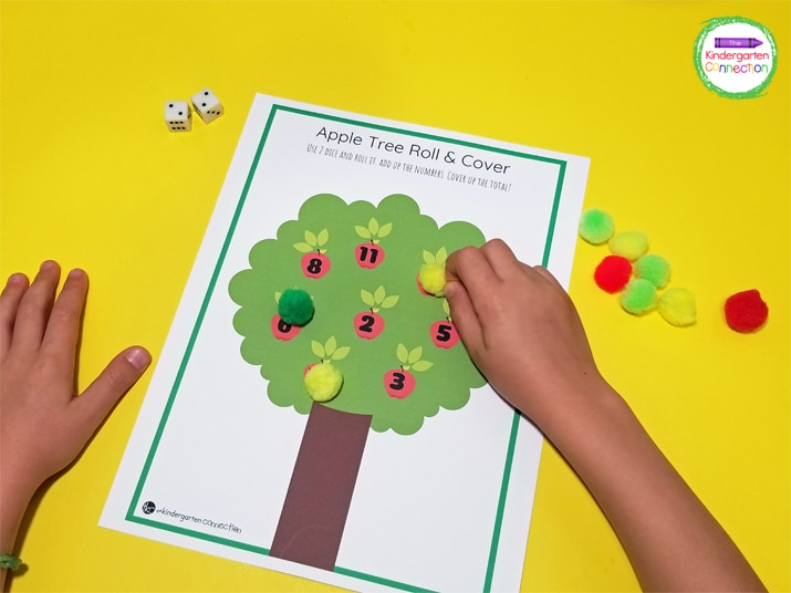 I used apple colored pom poms as our game pieces.