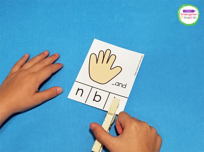 Students pick a card, identify the beginning sound, and clip the correct letter with a clothespin.