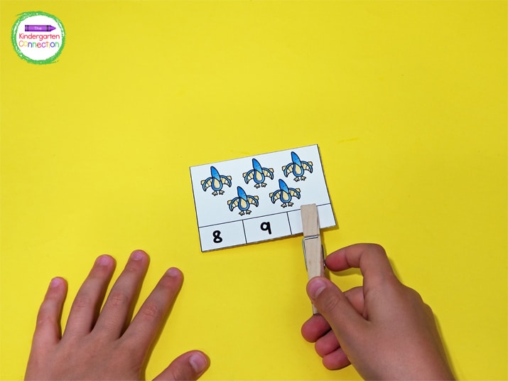 Students count the dinos on the cards and then use a clothespin to clip the correct number or number word.