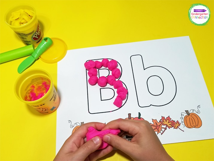 Students can fill the letters on the alphabet mats with balls of play dough.