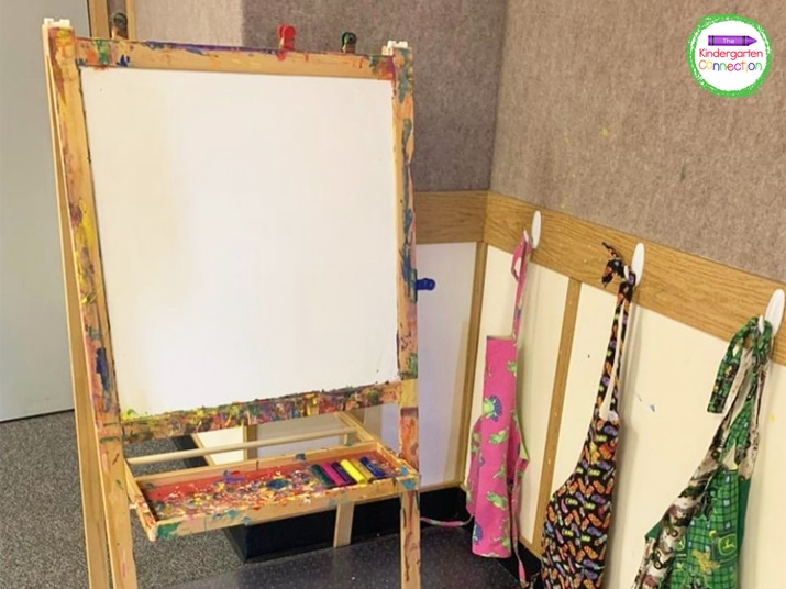 Start by setting up the easel with paint aprons or shirts that are within reach and accessible to students.