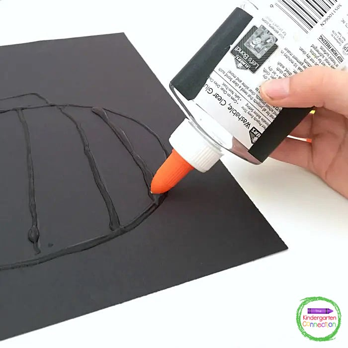 Use clear glue to trace the pencil lines of the pumpkin drawn on the construction paper.