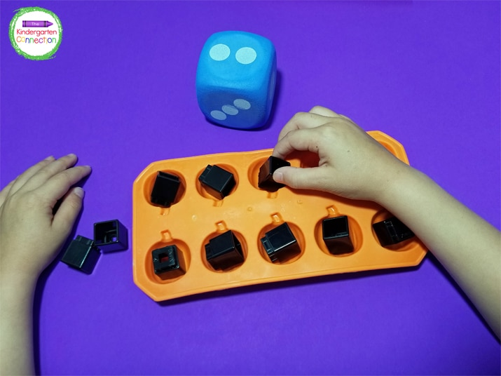 Kids take turns rolling the die, counting, and filling their ice try until they reach ten.