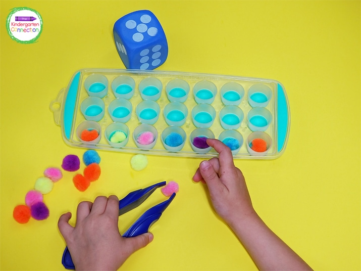 Add in a clothespin or jumbo tweezers for the kids to pick up the pom poms and place them into the ice cube trays.